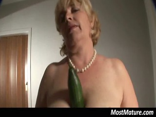 blond aged puts cucumber in her twat