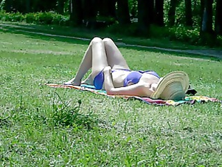 aged woman sunbathing in public park
